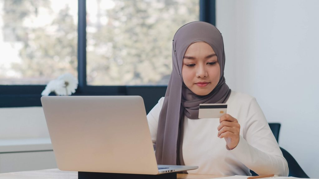 asian-muslim-lady-using-laptop-credit-card-buy-purchase-e-commerce-internet-office-min-1-scaled