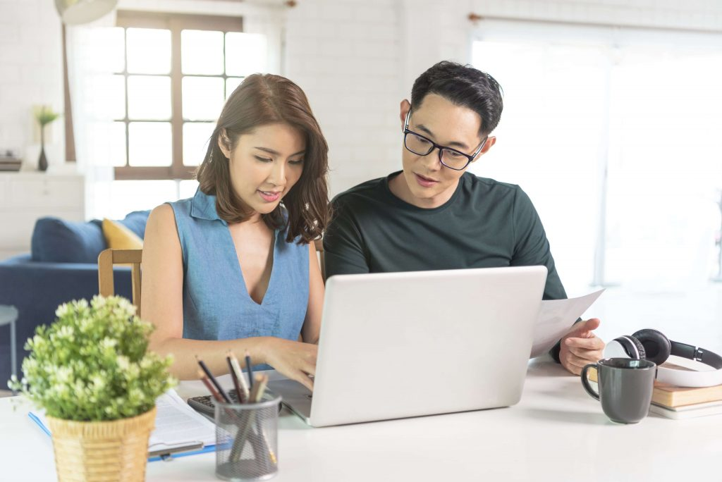 Asian couple analysing infront of a laptop