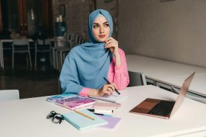 modern muslim woman woking with a laptop in an opened office