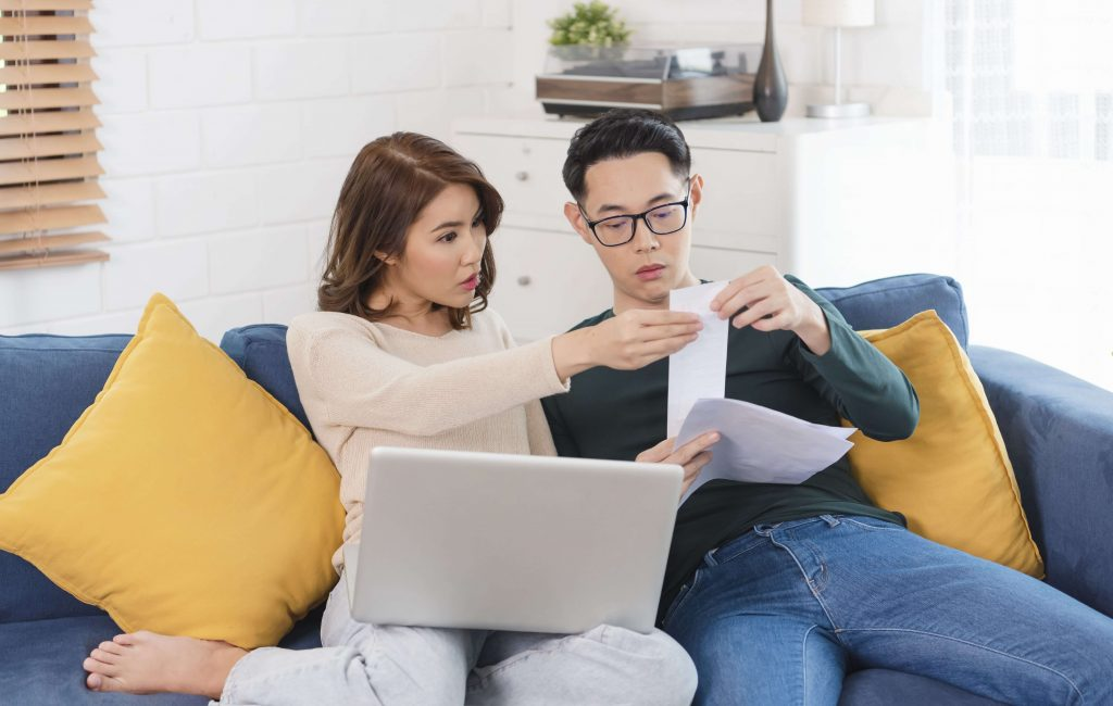 Asian couple sitting on a couch looking at bills and statements in front of a laptop together.